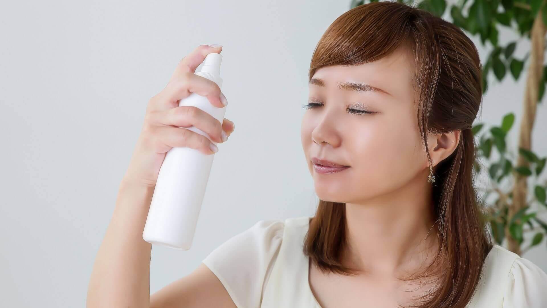 顔にミストを吹き付ける女性の画像